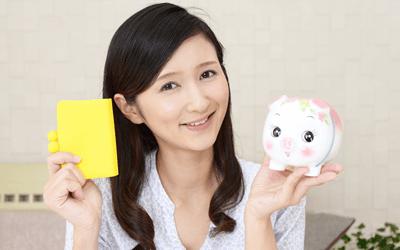 財布と貯金箱を持つ女性保健師