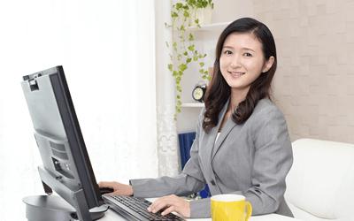 パソコンの前で微笑む女性